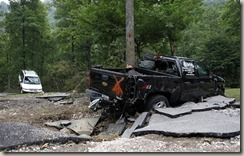 A truck and a van damaged by flash flooding are seen at Albert Pike campground near Caddo Gap, Ark., on Saturday.